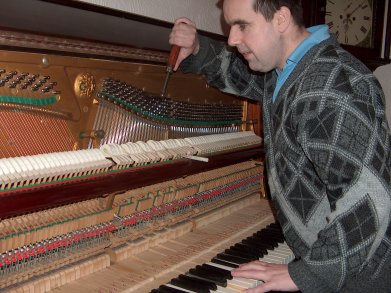 picture of piano tuner working on piano